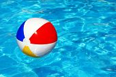 Beach ball floating in swimming pool abstract concept for summer vacations, relaxation and fun in the sunshine poster