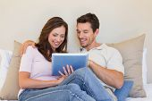 Happy relaxed young couple using digital tablet in the living room at home poster