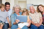 Happy multigeneration family using digital tablet at home poster