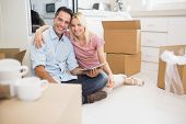 Portrait of a smiling couple using digital tablet amid boxes in a new house poster