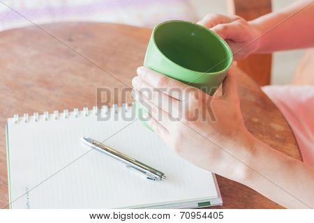Hand Holding Green Mug In Coffee Shop