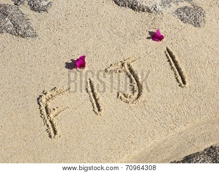 fiji written on a wet beach with pink flowers