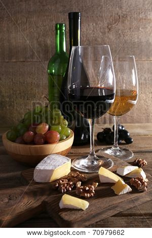 beautiful still life with wine, cheese and ripe grape on wooden background poster