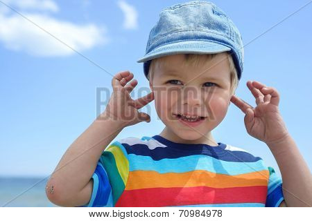 Portrait of small boy holds his hands over ears not to hear, horisontal poster