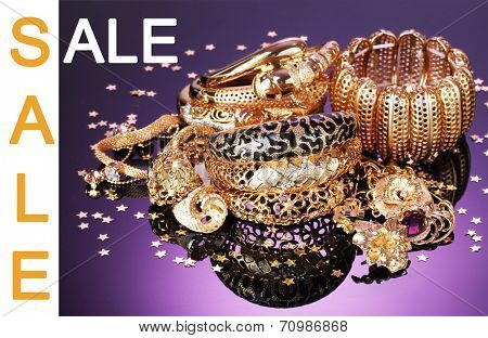 Concept of discount. Beautiful golden jewelry on purple background