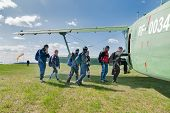 Yalutorovsk, Russia - May 24, 2008: Group of athletes-paratroopers gets into AN-2 plane. Sport airdrome poster