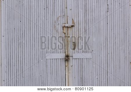 Old rusty metal padlock hanging on a weathered wooden door with rust staining the planks