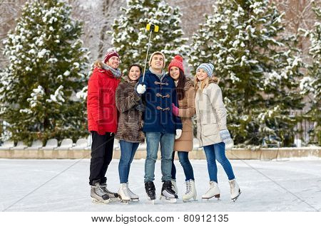 people, friendship, technology and leisure concept - happy friends taking picture with smartphone selfie stick on ice skating rink outdoors