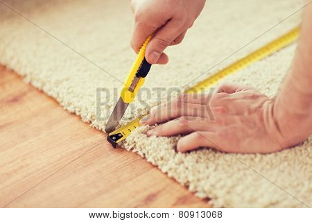 repair, building and home concept - close up of male hands cutting carpet with blade