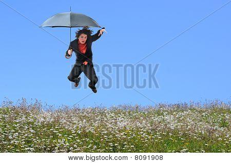 Businessman Jumping Over Grass Hill