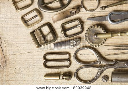 Leather craft toolsthread and buckles on a wooden background poster