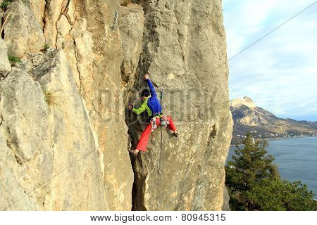 Climber.Man climbs up the wall on the background of mountains and sea. poster