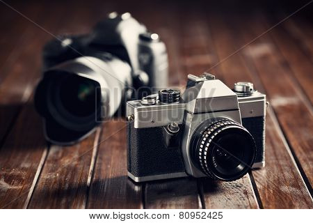 retro and dslr camera on wooden table
