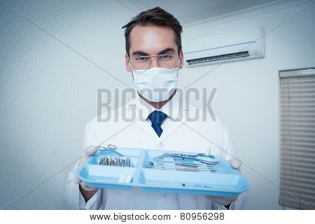 Portrait of male dentist in surgical mask holding tray of tools
