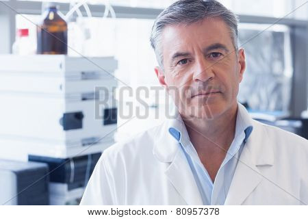 Portrait of an unsmiling scientist wearing lab coat in laboratory