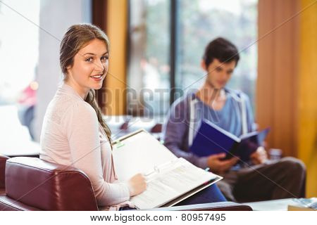 Students sitting on couch revising and smiling at camera at the university