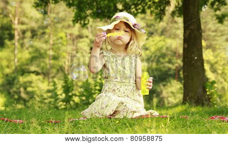a nice little girl with soap bubbles