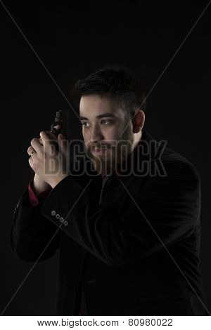 Half Body Shot of Gorgeous Goatee Man Wearing Black Suit Holding Small Black Gun. Isolated on Black Background. poster