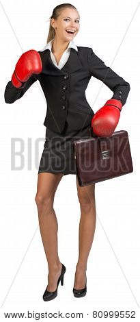 Businesswoman wearing boxing gloves holding briefcase, laughing