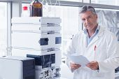 Scientist standing in lab coat holding a document in laboratory poster