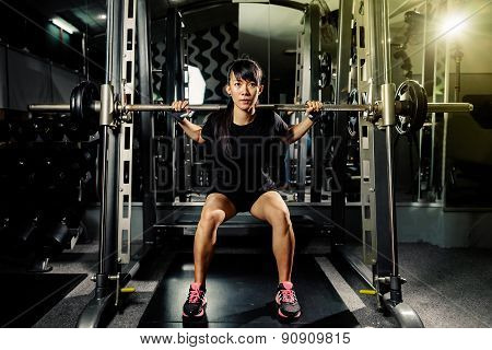 asian sexy fitness girl weightlifting in gym with heavy weights on black background poster