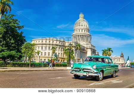 HAVANA, CUBA - DECEMBER 2, 2013: Old classic American grenn car rides in front of the Capitol. Befor