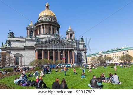 People Relax On The Grass In Front Of St. Isaac's Cathedral In St. Petersburg