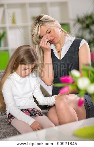 Sad girl sitting on sofa next worried mom at home