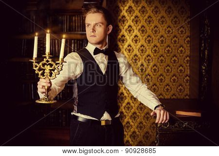 Young handsome man in formal suit and bow-tie stands with candles in a room with classic vintage interior. Fashion. Magic, halloween.