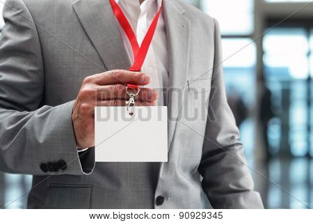 Businessman at an exhibition or conference showing a blank security identity name card on a lanyard