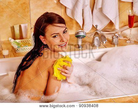 Young woman take bubble  bath. Home interior.