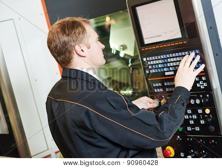 industrial worker programming cnc turning machine center for metal working at manufacture workshop