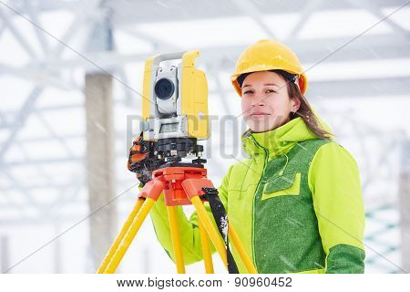 female surveyor worker working with theodolite transit equipment at building construction site outdoors