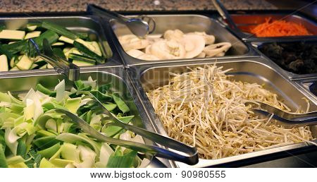 buffet restaurant with tray of bean sprouts and bamboo poster