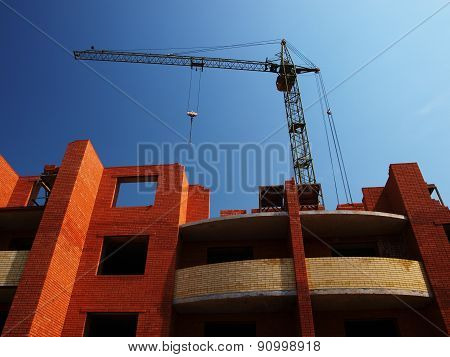 Multistory building from brick under construction with no roof and construction crane poster