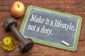 Make it a lifestyle, not a duty - fitness and healthy life concept  -  slate blackboard sign against weathered red painted barn wood with a dumbbell, apple and tape measure poster
