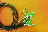 A group head connector fiber optic green color on brown table made with vintage color.Fiber Optics connectors. Internet Service Provider equipment. Focus on fiber optic cables. Data Network Hardware Concept. poster