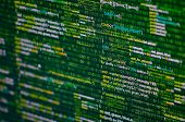 Programming abstract - source code and binary code on display of software developer. Green theme. poster