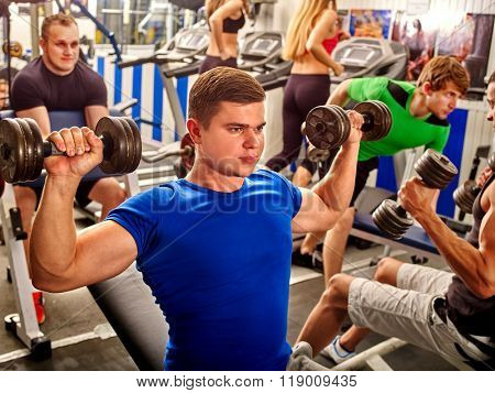Group of men working on simulator his body at gym. Man keeps dumbbells foreground