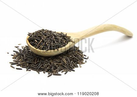 Wild rice in a wooden spoon on white isolated background