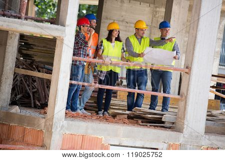 Young engineer team at construction place show building place as planned engineers, architects, team,