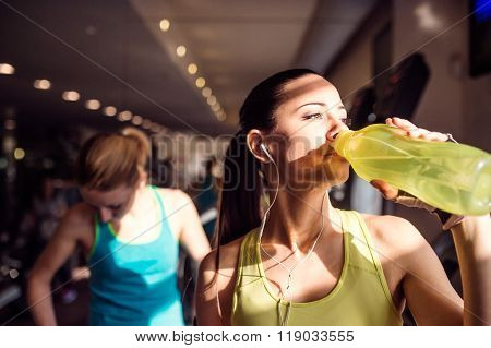 Two attractive woman in gym drinking water from bottle