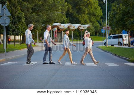 Happy group of seniors walking over crosswalk in a line