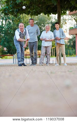 Senior people playing boule together in summer in city