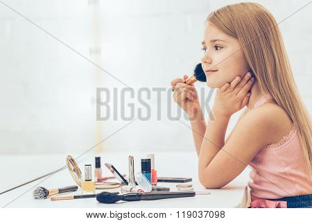 Adding some color to her cheeks. Side view of cheerful little girl applying make-up and looking at her reflection in mirror while sitting at the dressing table.