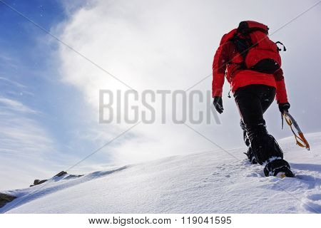 Mountaineer climbing a snowy peak in winter season. Concepts: determination, courage, effort, self-realization.
