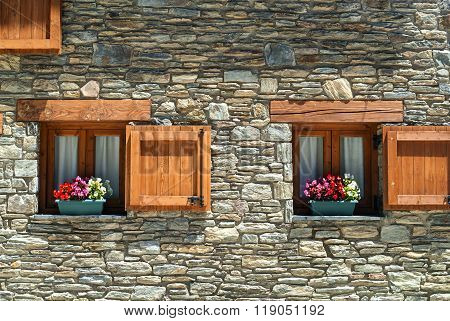 La Parroquia d'Horto (Catalunya Spain) old typical mountain village in the Pyrenees. Two windows with potted plants and flowers poster