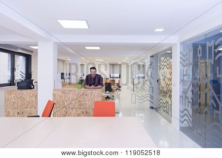 portrait of young business man in casual clothes sitting on table at  new startup office space and working on tablet computer