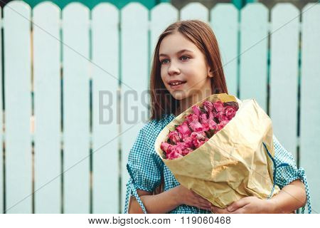 Tween girl holding a bunch of pink roses wrapped in craft paper over blue wooden fence
