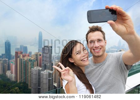 Multiethnic Chinese Caucasian couple in Hong Kong. Young people taking a smartphone selfie picture at viewpoint of famous attraction Victoria Peak, HK, China. Young multiracial group of people.